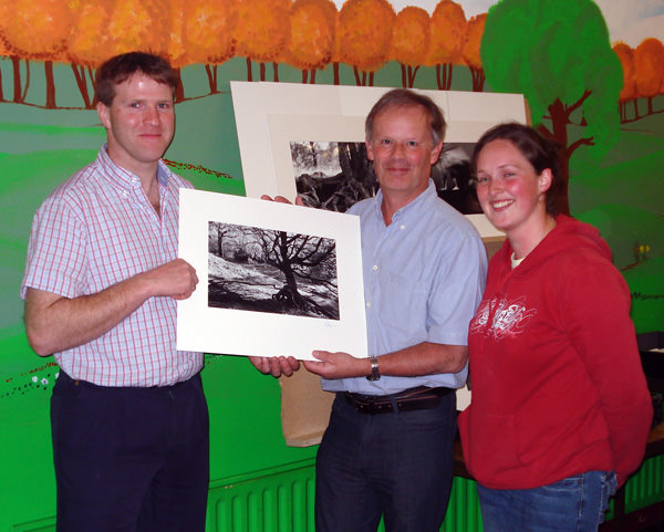 Roy Robertson presents a signed copy of one of his landscape photographs to John Hogan, club chairman, and Brd Coakley, to add to the club collection.